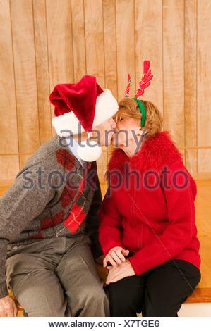 Couple de personnes âgées s'embrasser à Noël Banque D'Images