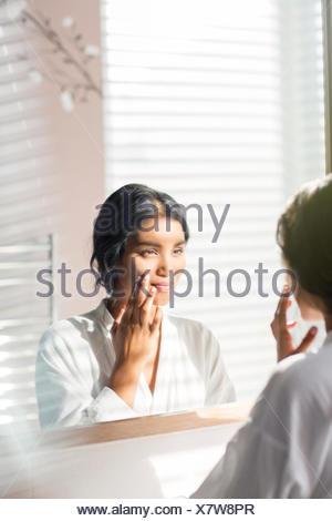 Woman applying moisturizer à face à miroir de salle de bains Banque D'Images