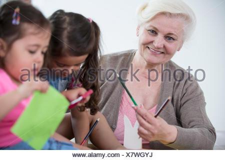 Portrait of senior woman helping petites-filles dans l'artisanat à la maison