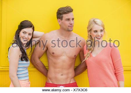 Portrait de l'homme dans les troncs entre deux femmes en face de fond jaune Banque D'Images