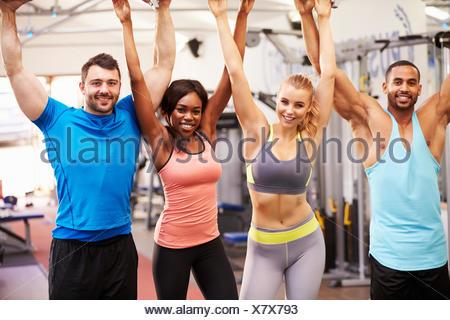 Heureux, groupe de personnes en bonne santé avec les bras en l'air dans une salle de sport Banque D'Images