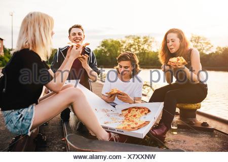 Amis assis ensemble à l'extérieur le partage d'une pizza Banque D'Images