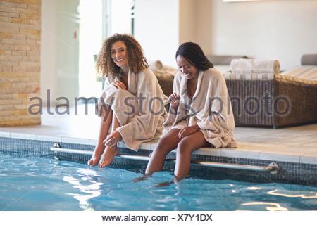 Deux jeunes femmes se détendre sur le bord du spa piscine Banque D'Images