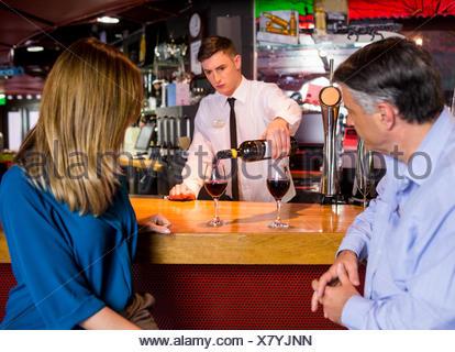 Barman offrant des verres de vin ou deux Banque D'Images