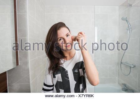 Portrait de femme belle appliquant le maquillage dans la salle de bains Banque D'Images