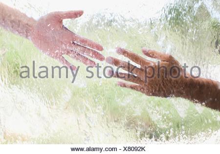 Deux mains tendues derrière une vitre Banque D'Images