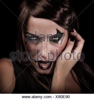 Effrayant portrait de jeune femme avec maquillage agressif isolé sur fond noir, terrifiant, sorcière, vampire Spooky Halloween party concept Banque D'Images