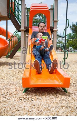 Jeune homme glisser vers le bas avec tout-petit frère sur l'aire de glisse Banque D'Images