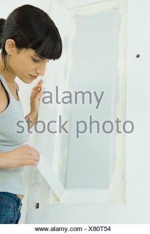 Woman ruban de masquage de boiseries fraîchement peint sur la porte Banque D'Images