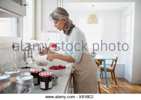 Femme faisant la confiture avec les baies fraîches dans la cuisine Banque D'Images