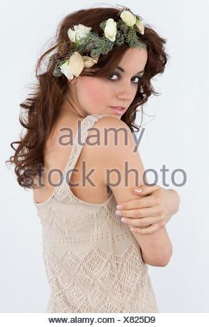 Jeune femme avec un arrangement floral comme une coiffe Banque D'Images