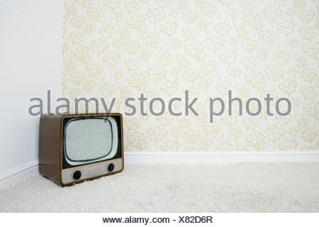 Retro télévision dans coin de la pièce avec du papier peint à motifs Banque D'Images