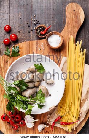 Ingrédients pour la cuisson des coquilles vongole spaghetti vongole, matières sapaghetti, les feuilles de persil, tomates cerises Banque D'Images
