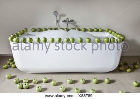 Baignoire remplie avec la pomme verte dans la salle de bains Banque D'Images