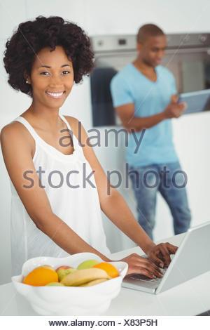 Femme souriante dans la cuisine using laptop Banque D'Images