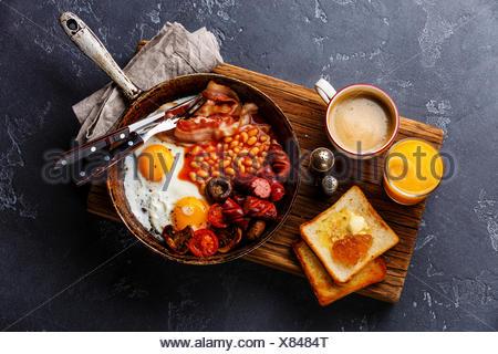 Le petit déjeuner anglais en plat de cuisson avec les œufs, saucisses, bacon, haricots, des toasts et du café à l'arrière-plan en pierre sombre Banque D'Images