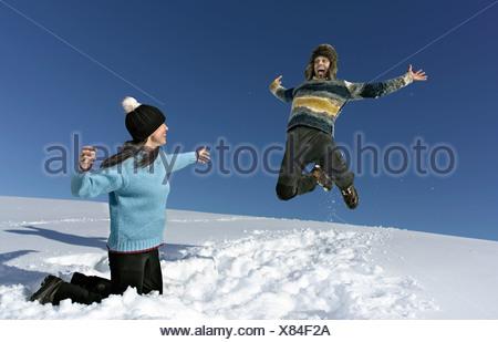 Couple jouent dans la neige, l'homme saute dans l'air Banque D'Images