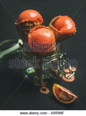 Orange sanguine d'été rafraîchissante glace ou d'un sorbet boules à cônes alvéolés doux dans un bocal en verre, fond sombre, selective focus