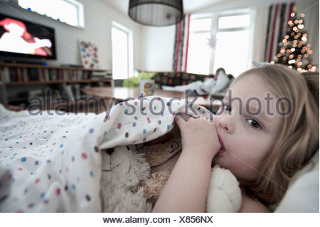 Girl resting in canapé blanc sucking thumb Banque D'Images