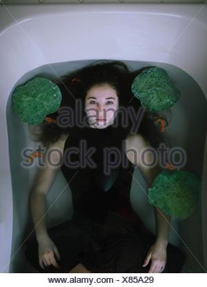 Vue aérienne d'une jeune femme couchée dans une baignoire avec poissons rouges et nénuphars Banque D'Images