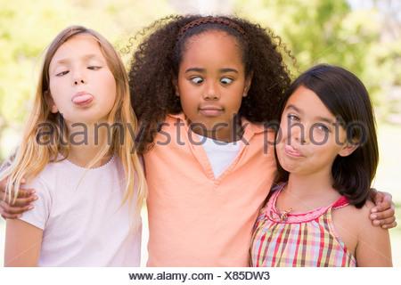 Trois jeunes girl friends outdoors making funny faces Banque D'Images