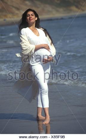 Mixed Race woman enceinte sur la plage de l'appareil photo en souriant Banque D'Images