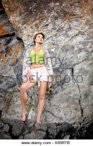Jeune femme debout à côté d'une falaise à la plage Banque D'Images