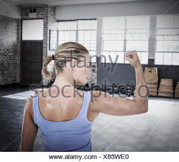 Image composite de la vue arrière de la woman flexing muscles Banque D'Images