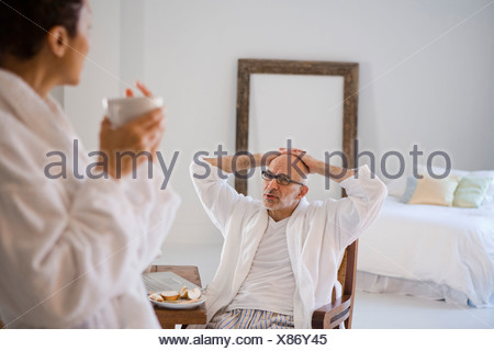 Femme mature tenant une tasse de café avec un homme mûr assis sur une chaise à l'arrière-plan Banque D'Images