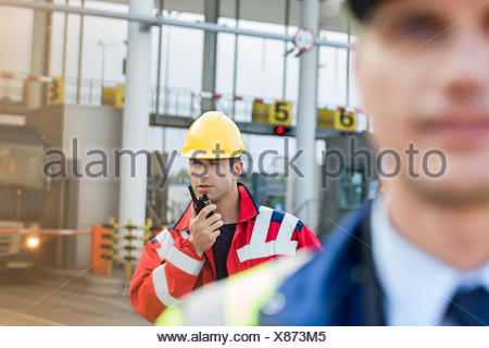 Travailleur à l'aide de talkie-walkie avec collègue en premier plan au Shipyard Banque D'Images
