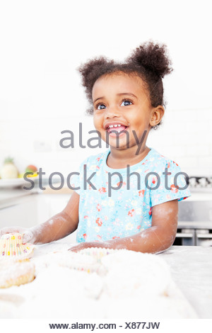 Smiling girl baking in kitchen Banque D'Images