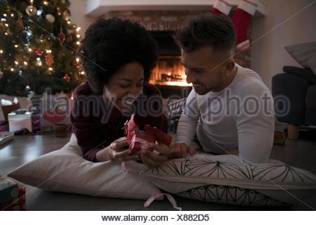 Jeune couple cadeau de Noël par un incendie dans la salle de séjour Banque D'Images