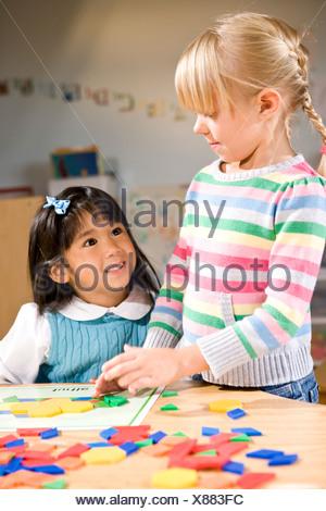 Deux enfants d'âge préscolaire qui travaillent ensemble sur la forme puzzle coloré Banque D'Images