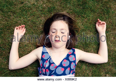 Girl lying on grass with earphones Banque D'Images