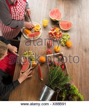 High angle view of Girl et grand-mère à la table de cuisine de fruits frais en tranches Banque D'Images