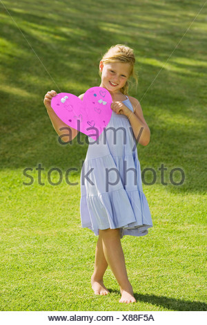 Young Girl holding du papier rose coeur Banque D'Images