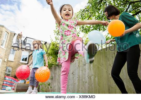 La mère et les filles jouant dans le jardin avec des ballons Banque D'Images