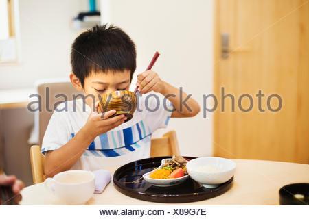 Maison de famille. Un garçon pour prendre un repas. Banque D'Images