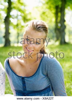 Jeune femme assise, smiling Banque D'Images