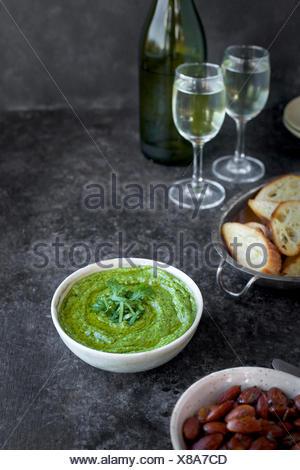Pesto de basilic ciboulette roquette servi dans un bol en céramique avec crostini, amandes et vin. Photographié de vue de face sur un fond marron/noir. Banque D'Images