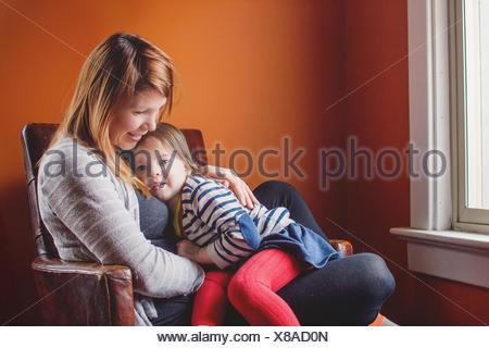 Mère et fille assise sur une chaise ensemble Banque D'Images