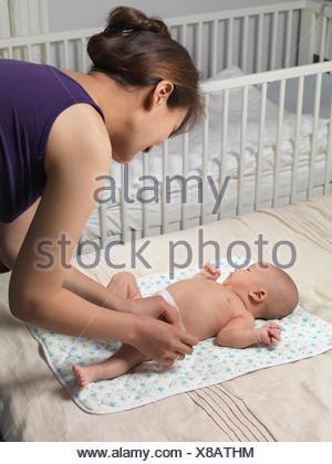 Mère changé une couche d'un bébé de six semaines boy lying on a bed