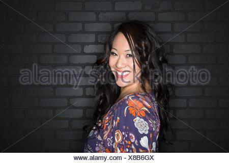 Portrait of smiling brunette wearing blouse à motifs Banque D'Images