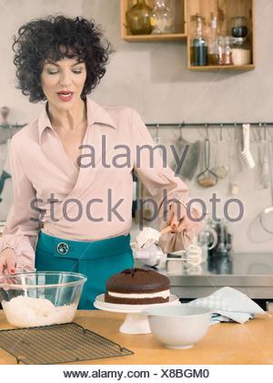 Woman decorating gâteau au chocolat avec crème de lait Banque D'Images