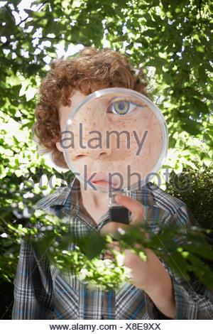 Jeune garçon à l'extérieur à travers une loupe Banque D'Images