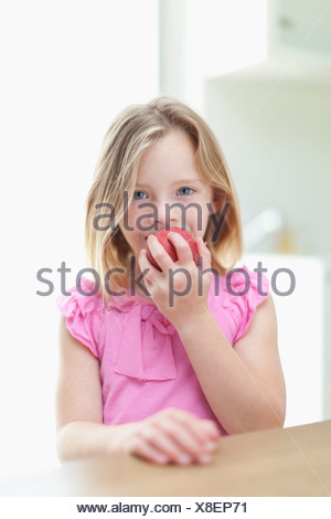 Girl eating apple en cuisine Banque D'Images