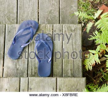 Les tongs sur terrasse en bois Banque D'Images