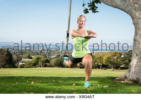 Jeune femme à l'aide d'une fente de corde en park Banque D'Images