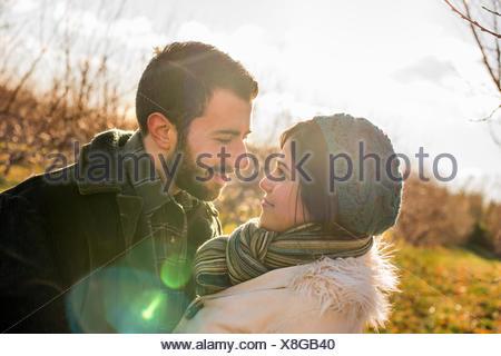 Deux personnes, un couple en train de marcher dans un verger en hiver. Banque D'Images