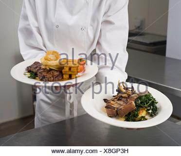 Un chef holding deux dîners plaqué Banque D'Images